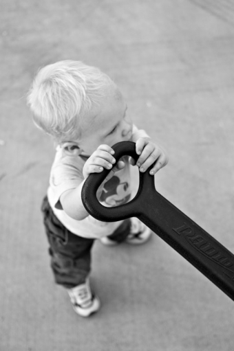 A toddler holds up the handle of his wagon