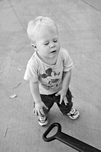 A toddler slams his wagon handle to the ground