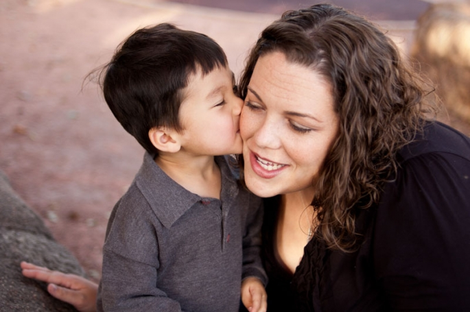 Portrait of a three year old boy kissing his mother