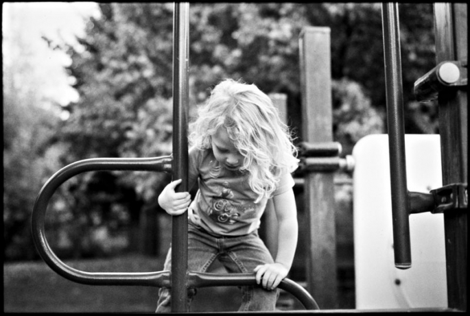 Little girl climbing on playground equipment
