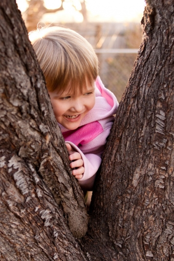 Three year old girl leaning against a tree