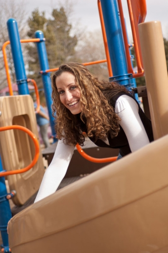 Young woman smiling while climbing on playground equipment