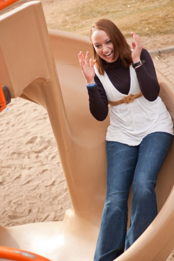 Young woman laughing while going down a slide