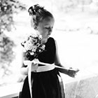 The Flower Girl inspects the ribbon on her bouquet