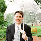 The Groom stands for a portrait in the rain
