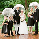 The full bridal party standing for a portrait in the rain