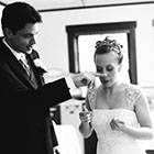 The Groom wipes frosting from the Bride\'s nose