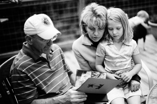 A couple looks at a photo album with their granddaughter