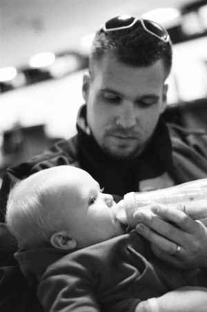 Father feeds his infant son a bottle