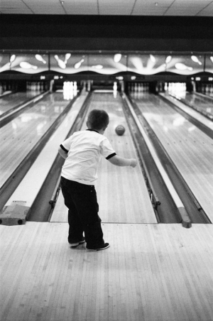 A five year old boy watches his ball roll down the lane