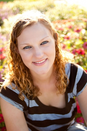 Senior portrait of a young woman sitting in a flower garden