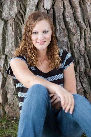 Senior portrait of a young woman sitting in front of a tree
