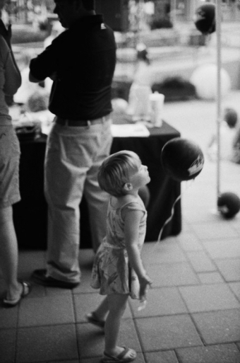 Little girl blowing a black balloon