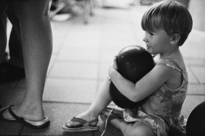 Little girl holding a black balloon