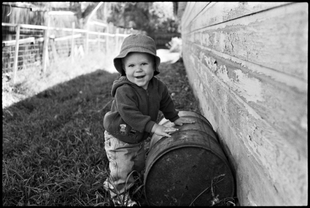 A toddler plays with an old barrel
