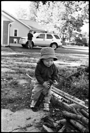 A one year old boy plays with a stick