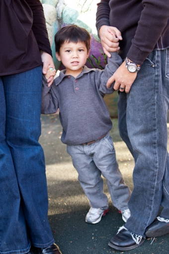 Portrait of a three year old boy standing between is parents