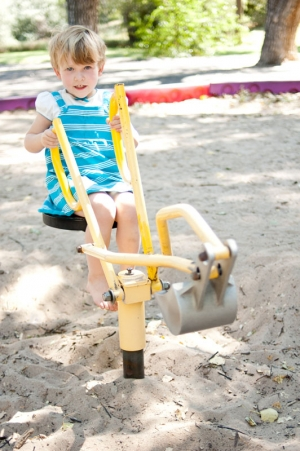 Three year old girl playing on a digging machine
