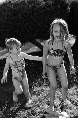 Young sisters playing in the sprinkler
