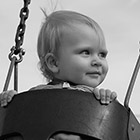 Portrait of a baby girl in a park swing.