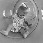 A toddler scoots through a tunnel