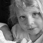 Portrait of a young girl holding her baby sister