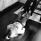 A two year old girl lays on the floor