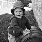 A toddler plays with and old barrel