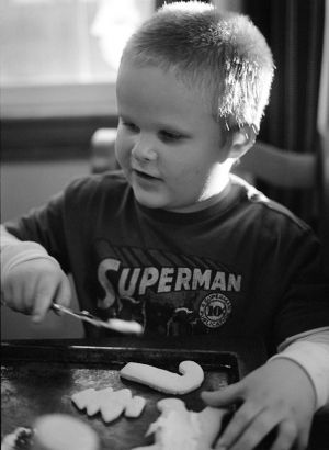 Documentary portrait of a 5 year old boy frosting cookies at the kitchen table. Shot on a medium format camera using black and white film.