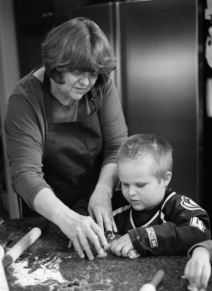 Family portrait of a Grandmother and grandson baking cookies at home in the kitchen. Shot on a medium format camera using black and white film.