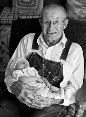 Infant girl being held by her great grandfather