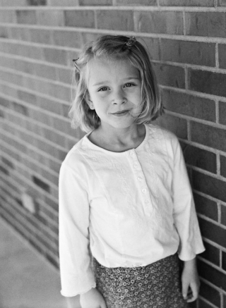 Portrait of a five year old girl standing against a brick wall. Photographed at a farmhouse in rural eastern Colorado, on a Mamiya 645AF using Ilford HP5 film.