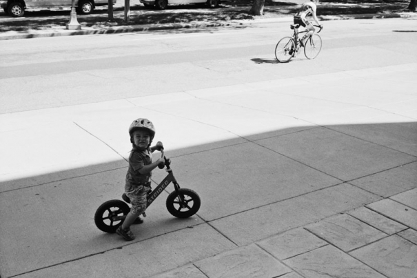 A young boy watches cyclists pass by
