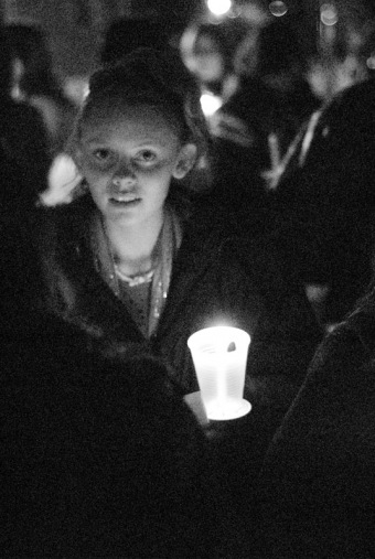 A girl's face is lit up by her candle