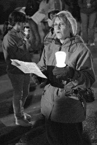 A woman holds a candle and sings