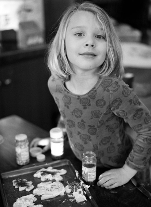 Documentary portrait of a 5 year old girl decorating cookies at the kitchen table. Shot on a medium format camera using black and white film.