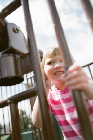 A two year old girl looks through a telescope on the playground at Nottingham Park in Westminster, CO. Photograph from a documentary portrait session using Fuji 400H film in a Nikon N90s camera.