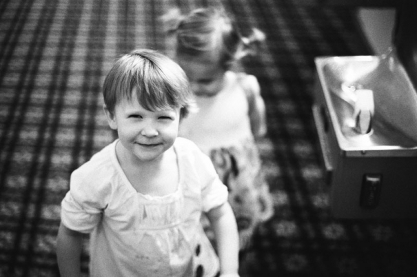 A two year old girl looks suspiciously at the camera. Picture from a hotel reception the night before a Bat Mitzvah in Salt Lake City, Utah.