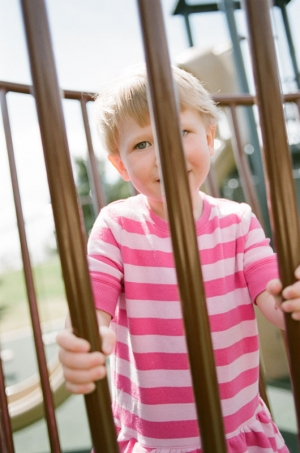 A two year old girl peers through bars on the playground at Nottingham Park in Westminster, CO. Photograph from a documentary portrait session using Fuji 400H film in a Nikon N90s camera.