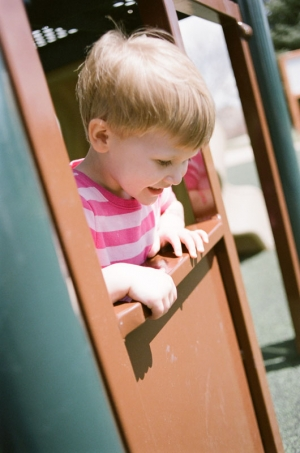 A two year old girl looks through a playhouse window on the playground at Nottingham Park in Westminster, CO. Photograph from a documentary portrait session using Fuji 400H film in a Nikon N90s camera.