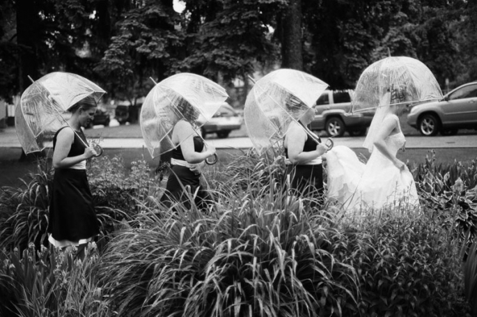 Bride and her bridesmaids walking in the rain