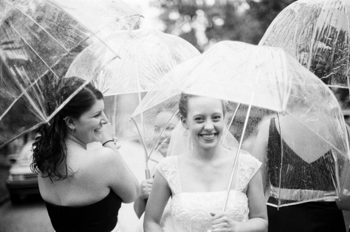 Bride and her bridesmaids standing in the rain