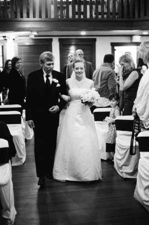 The father of the bride escorts his daughter up the aisle