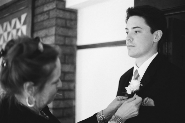 Groom has his boutonniere pinned on