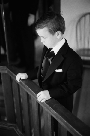The ring bearer, in his tuxedo, stands at a balcony railing