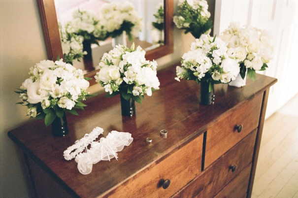 Bouquets, garters, and rings set on a dresser