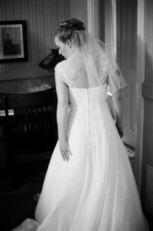 The bride adjusts her dress