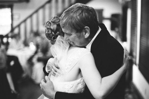 The father of the bride and his daughter share a hug