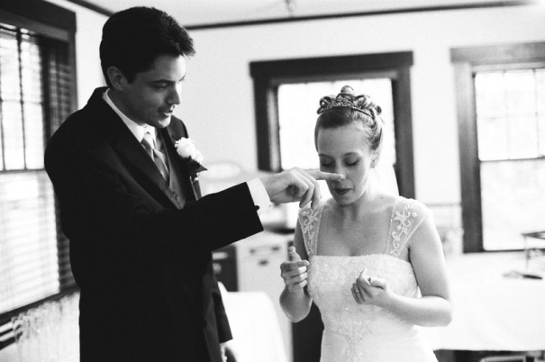 The Groom wipes frosting from the Bride's nose