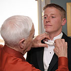 Grandfather adjusts groom's tie.